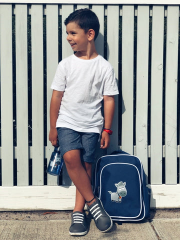 Boy leaning against a fence, holding an indigo Jordbarn water bottle and backpack by his side
