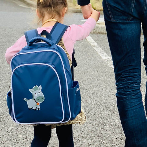 Girl walking down the street wearing a blue Jordbarn blue backpack and holding her dad's hand
