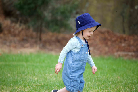 Boy running at the park with a Jordbarn Indigo bucket hat
