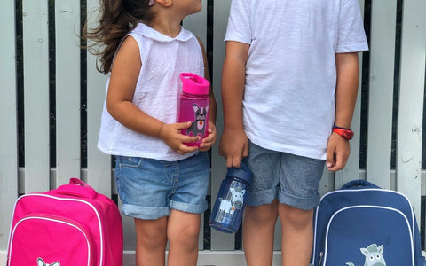 Two kids looking at each other holding Jordbarn backpacks and water bottle