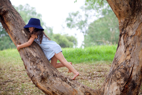 Girl climbing a tree wearing a Jordbarn Indigo Bucket Hat