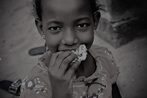 African girl smiling eating a biscuit