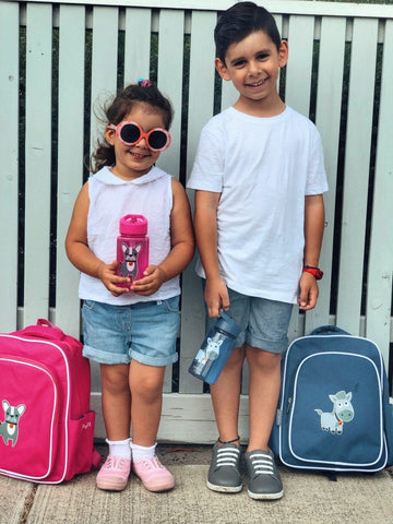 Two kids facing front, with Jordbarn backpacks and water bottle