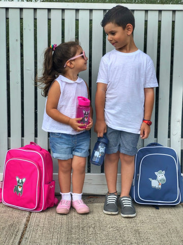 Two kids looking at each other with magenta and indigo backpacks by their side, holding water bottle