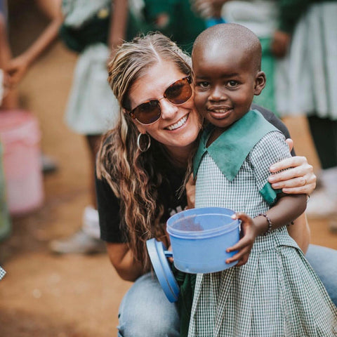 Smiling lady with happy Nairobi child holding a blue bucket