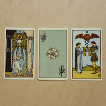 Load image into Gallery viewer,  Three tarot cards, left to right:  The High Priestess, a back of a card featuring Pixie's signature and a white Tudor style rose on light blue, two of cups.