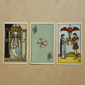 Three tarot cards, left to right:  The High Priestess, a back of a card featuring Pixie's signature and a white Tudor style rose on light blue, two of cups.