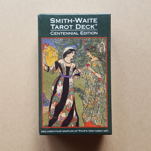 Front cover of Smith-Waite Centennial Edition tarot deck's box.  Box is bordered with dark green, text is in white, and artwork features two people in ornate flowing gowns talking, with a third person in a gown in the upper left background.