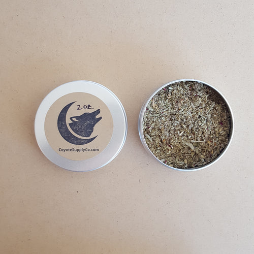 Left: round aluminium tin lid with round kraft label that has been hand stamped with the Coyote Supply Co. logo of a crescent moon cradling a howling coyote head.  Right: round aluminium tin full of ground herbs and spices.