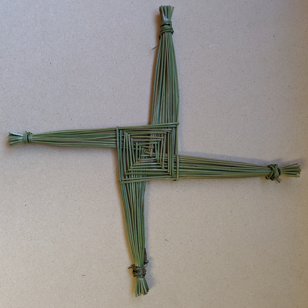 A squared off cross, called a Brigid's Cross, made of green rushes on particle board background.