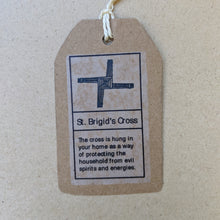 "Load image into Gallery viewer, Detail of kraft paper hang tag that accompanies each cross.  Top has black drawing of the cross, bottom text reads ""The cross is hung in your home as a way of protecting the household from evil spirits and energies."" in black ink."