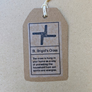 "Detail of kraft paper hang tag that accompanies each cross.  Top has black drawing of the cross, bottom text reads ""The cross is hung in your home as a way of protecting the household from evil spirits and energies."" in black ink."