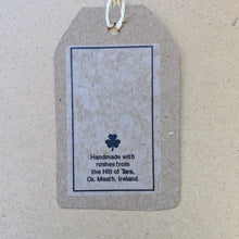 "Load image into Gallery viewer, Detail from back of kraft paper hang tag that accompanies each cross.  Small clover and text that reads ""Handmade with rushes from the Hill of Tara, Co. Meath, Ireland."" in black ink."