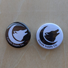 Load image into Gallery viewer, Two buttons featuring the Coyote Supply Co. logo of a crescent moon cradling a howling coyote head.  Left button is the logo in white on a black background, right button is the logo in black on a white background.