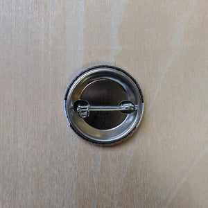 Back of metal button features a pin back closure.