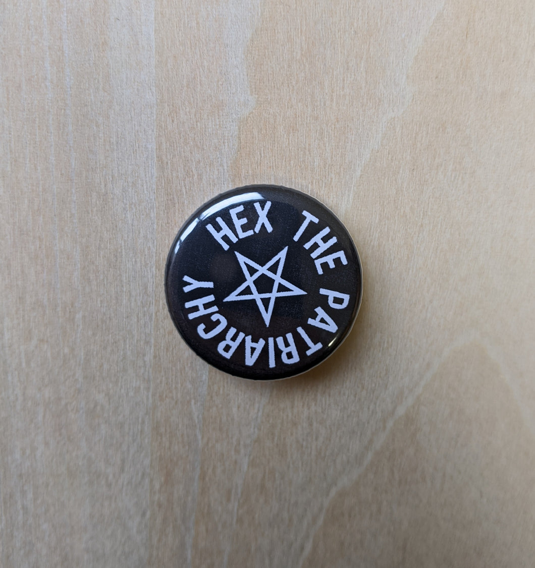 White text on round black button reads: Hex the Patriarchy, surrounding a white pentagram