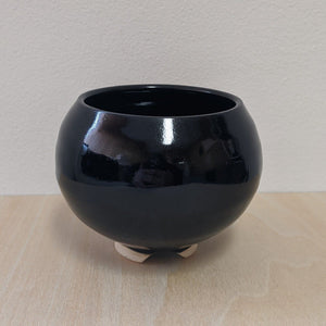 Black ceramic cauldron on wood surface with white background.