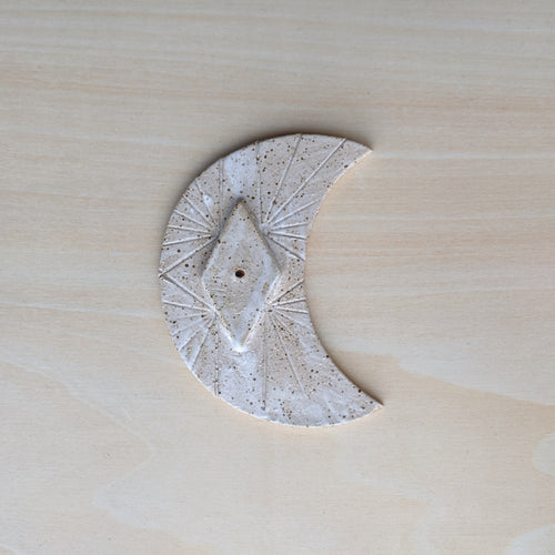 White ceramic crescent moon incense burner.