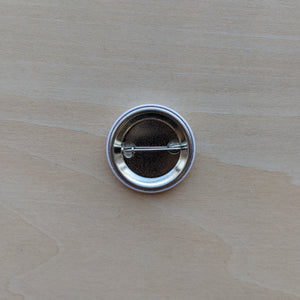 Metal button back features a pin style back.