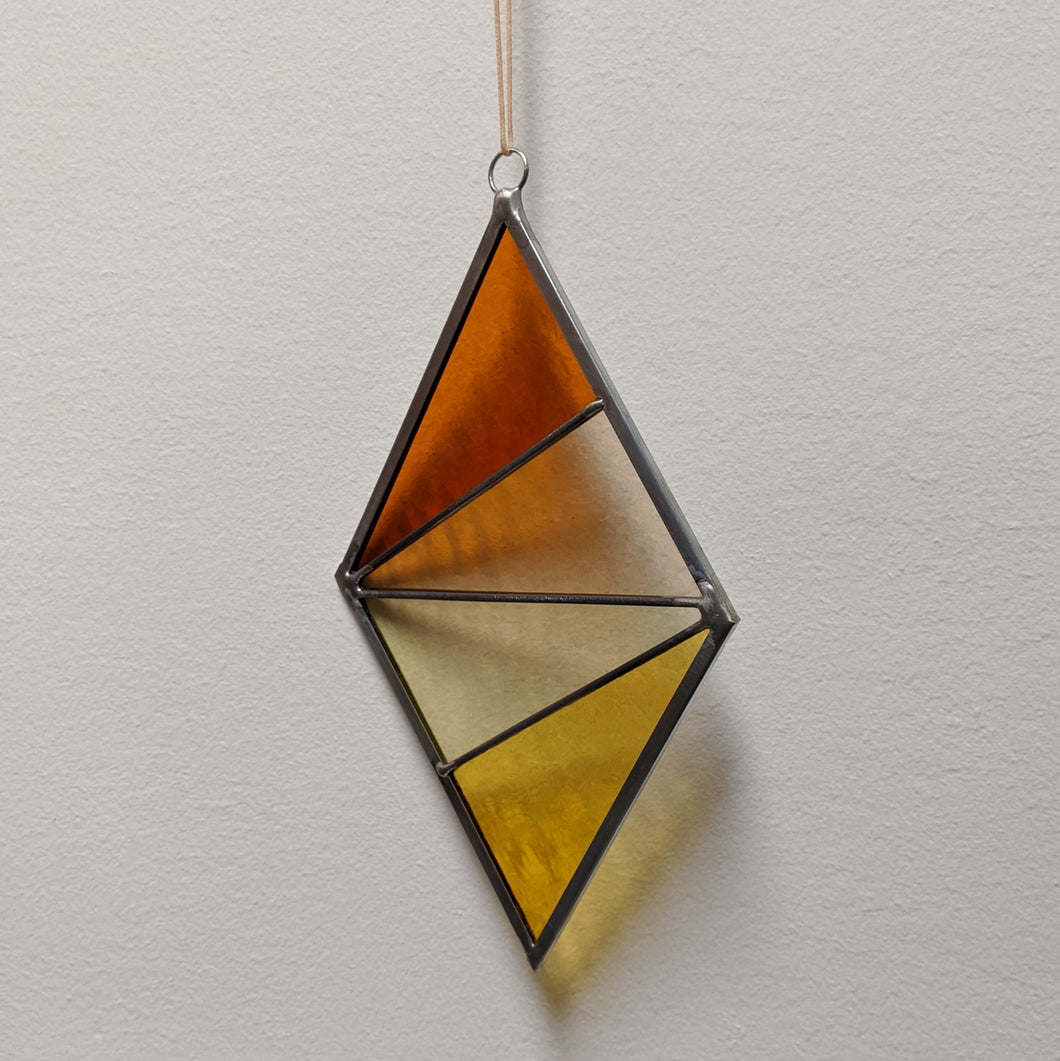 Diamond stained glass suncatcher with four colors from top to bottom: pumpkin, peach, pale green, & sunflower yellow.