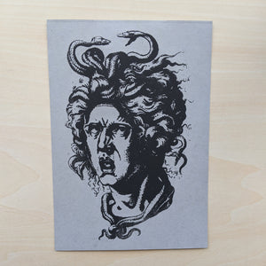 Black medusa head printed on grey paper.