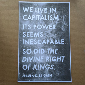 "White text on black galaxy photo reads: ""We live in capitalism.  Its power seems inescapable.  So did the divine right of kings.  Ursula K. Le Guin"""