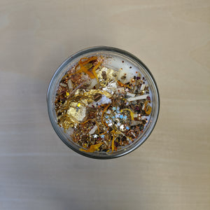 White soy wax candle topped with confetti, herbs including marigolds, and gold leaf.