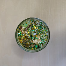 Load image into Gallery viewer, Green soy wax candle topped with glitter, sesame seeds, a penny, and gold leaf.