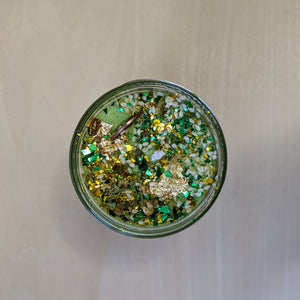 Green soy wax candle topped with glitter, sesame seeds, a penny, and gold leaf.