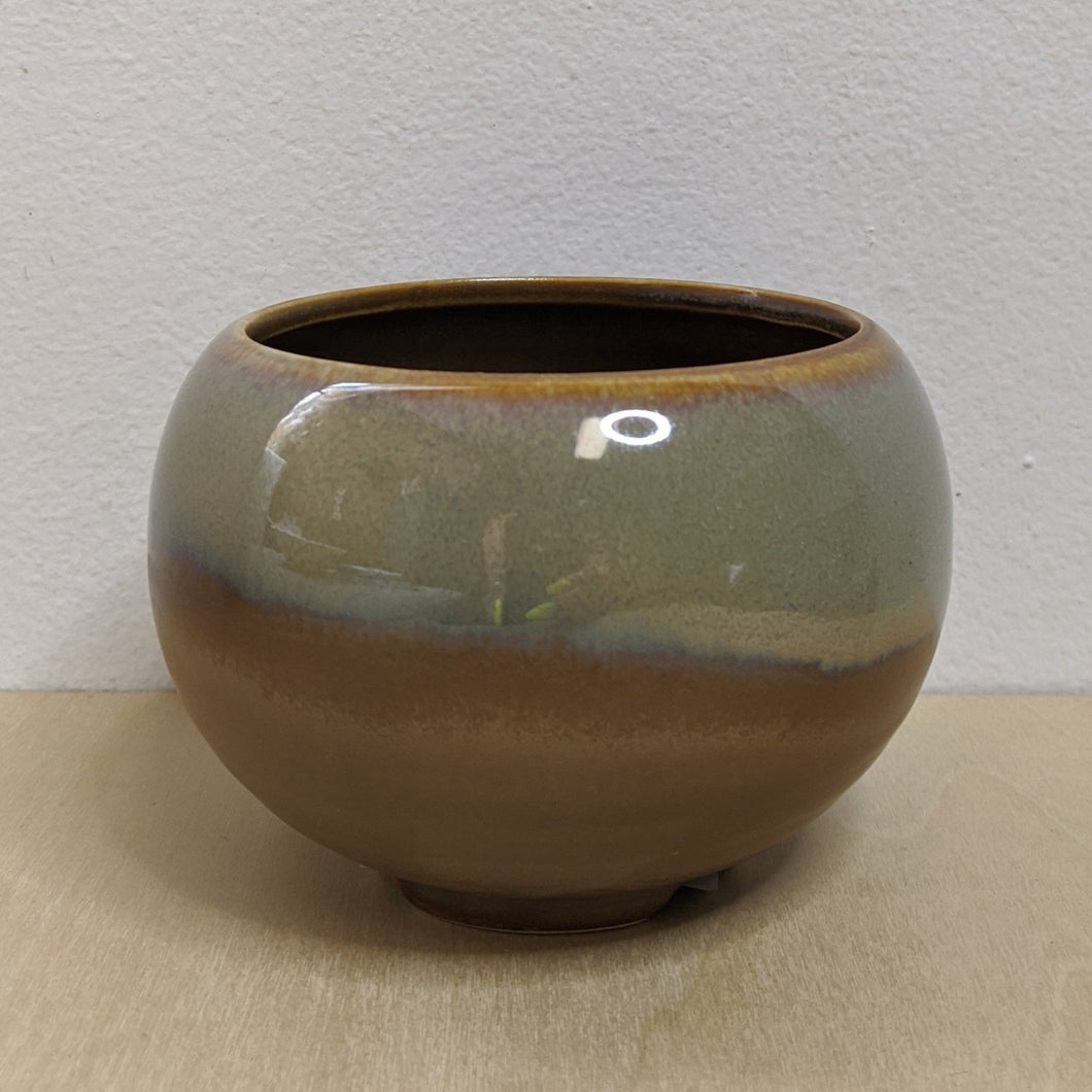 Matte tan cauldron with a shiny sagebrush green glaze edged in lavender.