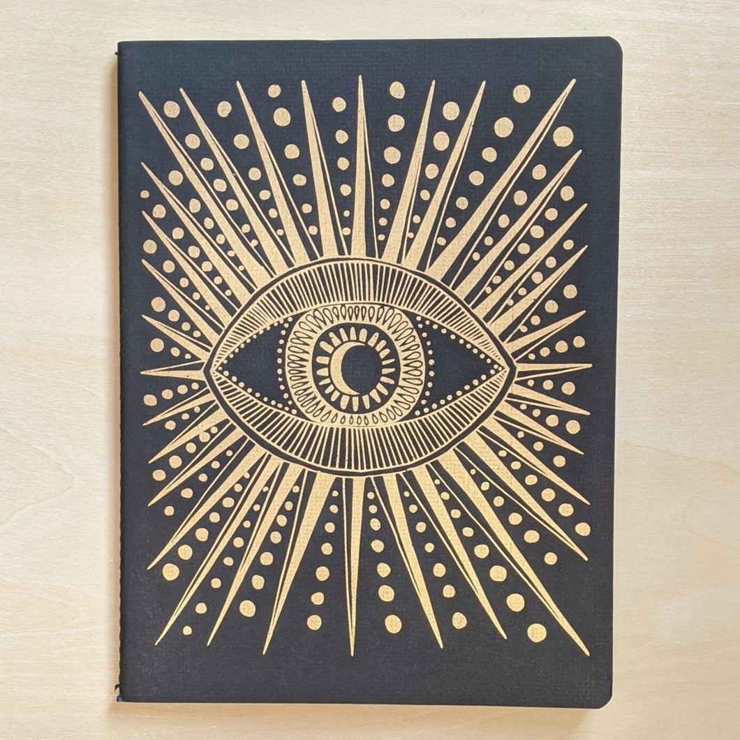Gold eye with starbursts & dots on black paper.