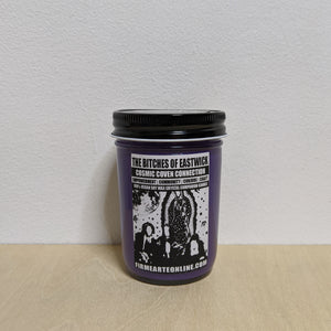 Purple soy wax candle in glass jar with black lid.  Features white label with black artwork of the characters from The Craft & The Virgin of Guadalupe.