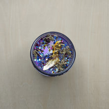 Load image into Gallery viewer, Purple soy wax candle topped with gold leaf, glitter, star confetti, and mugwort.