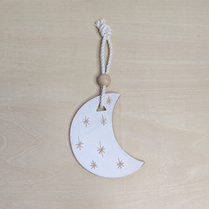 Matte white ceramic crescent moon with light terra cotta starbursts, hanging from white cotton cord, topped with a round wooden bead.