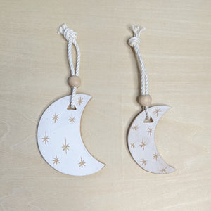Two matte white ceramic crescent moon with light terra cotta starbursts, hanging from white cotton cord, topped with a round wooden bead. The one on the left is larger.