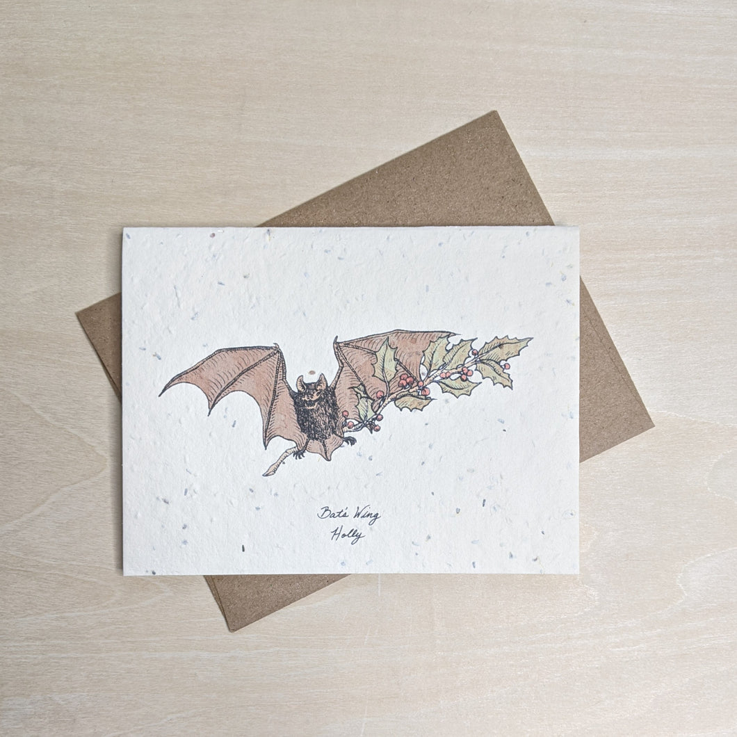 Bat carrying a holly sprig watercolor on white seed paper with a kraft envelope.