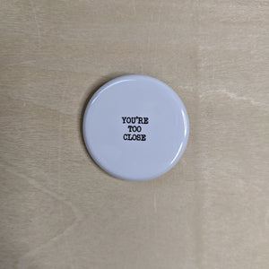 "Black text on shiny white button reads ""You're too close."""