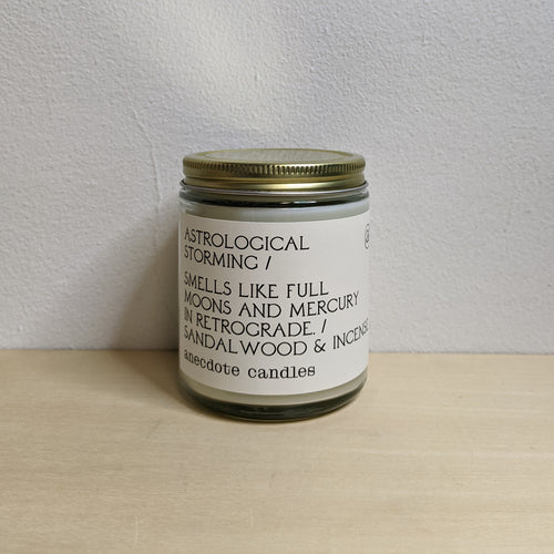 White soy wax candle in clear glass jar with gold lid & white label with black text.