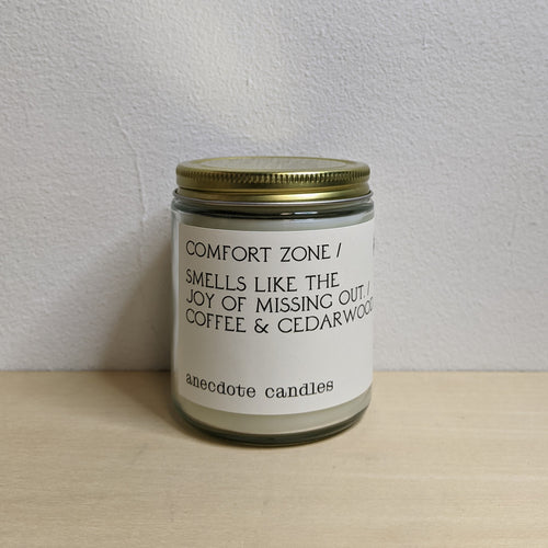 White soy wax candle in a clear glass jar with gold lid, featuring a white label with black text.