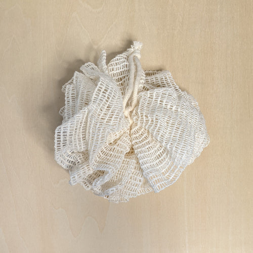 Undyed ramie mesh bath pouf with hanging loop.