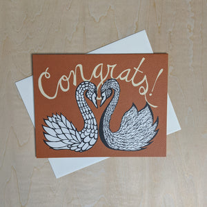 "Orange paper card featuring a drawing of a black swan and a white swan with ""congrats!"" in script at the top"
