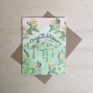 "Pink to green watercolor card with peach and yellow flowers & black ""congratulations"" in script.  Show with kraft envelope."