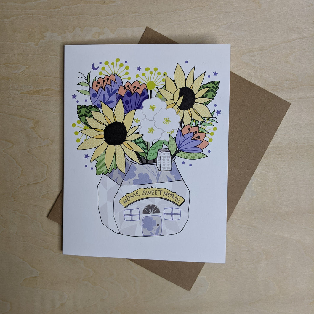 White paper card with a tulip & sun flower bouquet in a house shaped vase.  Vase reads