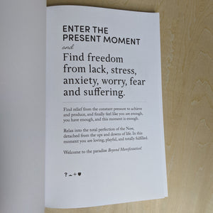 "white page with black text reads ""enter the present moment & find freedom from lack, stress, anxiety, worry, fear, and suffering"" with a paragraph underneath"