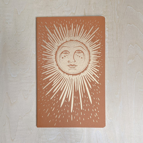 Notebook cover featuring a gold sun on terracotta paper.
