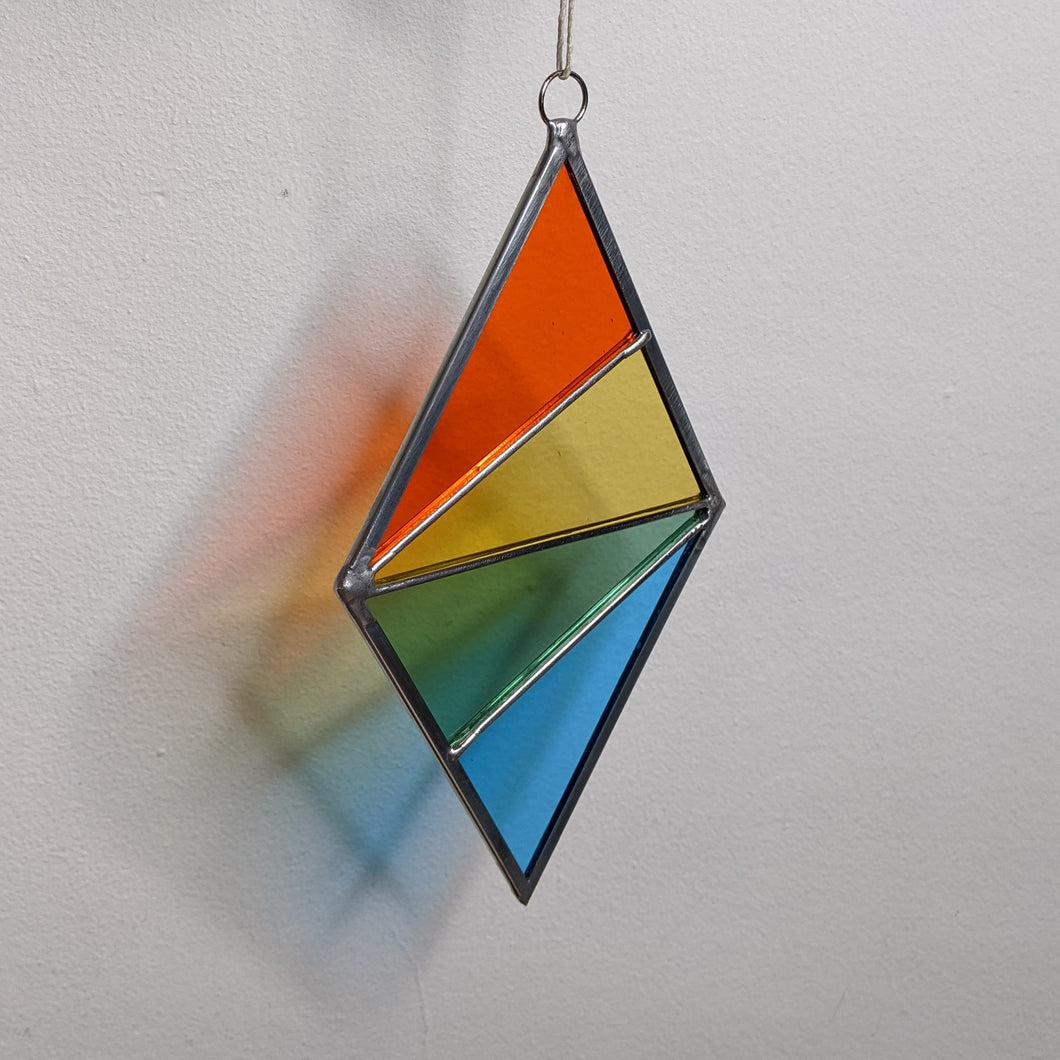 Diamond stained glass suncatcher with orange, yellow, green, & turquoise triangles.