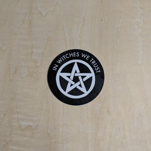 "Black round sticker with a white pentagram in the middle & the phrase ""In witches we trust"" across the top"