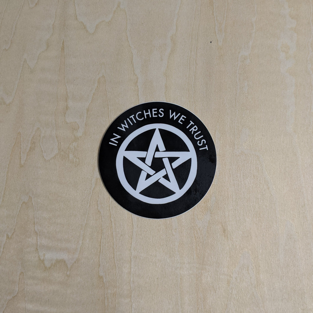 Black round sticker with a white pentagram in the middle & the phrase