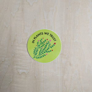 "Lime green round sticker with the text ""in plants we trust"" at the top in black & a pink & green floral sprig at the bottom"