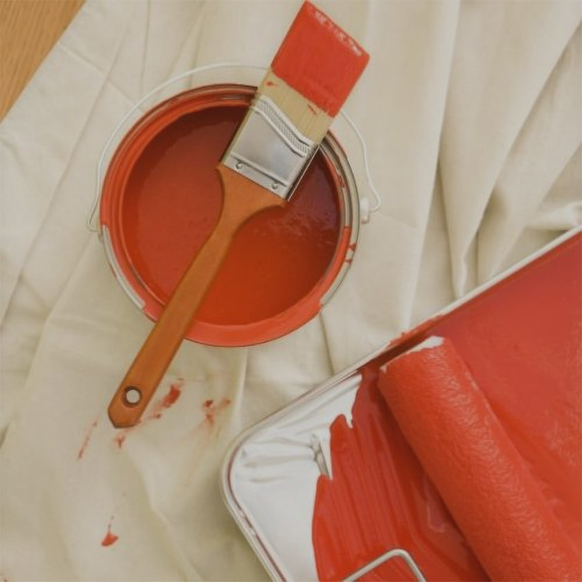 paint can with paint brush, tray & tray liner and roller on a drop cloth
